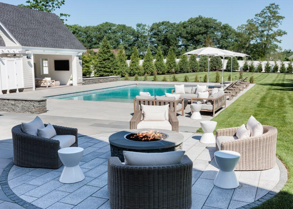 patio with fire pit, pool house and pool